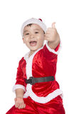 Funny boy in a Christmas hat isolated on white background. Laughing funny child in a Christmas hat, showing thumbs up. Isolated on white background stock photo