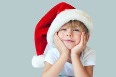 Funny Boy in Christmas Santa Hat Isolated Grey. Funny Boy in Christmas Santa Hat with Smile on Face Christmas theme Isolated Grey Stock Images