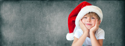 Funny Boy in Christmas Santa Hat Isolated Grey. Funny Boy in Christmas Santa Hat with Smile on Face Christmas theme Isolated Grey Stock Photography
