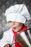 Funny boy cook in uniform over vintage  background playing with. Cookware, cooking Stock Images