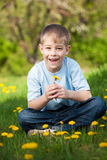 Funny boy with dandelions in a green park. summer Royalty Free Stock Photography