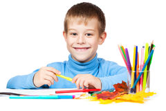 Funny boy is drawing with pencils Royalty Free Stock Photos