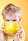 Funny boy drink from big yellow cup Stock Photography