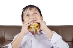 Funny boy eating a cheeseburger Stock Photo