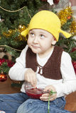 Funny boy eating jam. Sitting under the christmas tree Stock Photo
