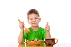 Funny boy eating oatmeal at the table stock photos