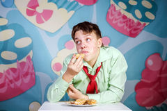 Funny boy eating sweet cakes, hungry and candy man Stock Photo