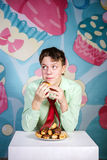 Funny boy eating sweet cakes, hungry and candy man Stock Photography