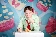 Funny boy eating sweet cakes, hungry and candy man Royalty Free Stock Photos