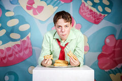 Funny boy eating sweet cakes, hungry and candy man Stock Photos