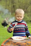 Funny boy eats sausages on picnic Royalty Free Stock Image