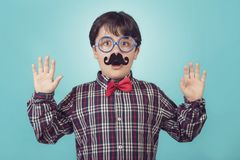 Funny boy with fake mustache and tie. On blue background royalty free stock photography