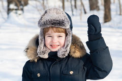 Funny boy in a fur hat on a cold winter day Stock Image