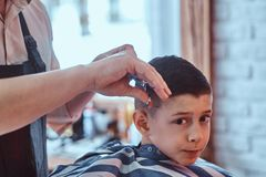 Funny boy is getting trendy haircut from expirienced barber at fashionable hairdressing salon at firs time. Funny little boy is getting trendy haircut from stock photo