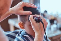Funny boy is getting trendy haircut from expirienced barber at fashionable hairdressing salon at firs time. Funny little boy is getting trendy haircut from royalty free stock images