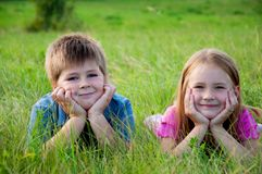 Funny Boy and girl on grass Stock Photos