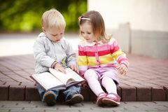 Funny boy and girl reading book Stock Photo