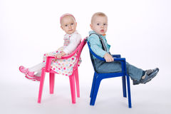 Funny boy and girl sitting on chairs back to back. Beautiful funny boy and girl sitting on chairs back to back Royalty Free Stock Photography