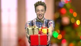 Funny boy giving you Christmas gift boxes.