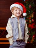 Funny boy in hat of Santa Claus standing in front of the tree da. Rk wood wall Royalty Free Stock Photo