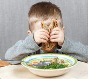 Funny boy hiding his face behind piece of bread Stock Photos