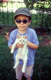 Boy holding cat. Funny boy holding his cat pet. 35mm film scan Stock Image