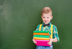 Funny boy holds a stack of heavy books near empty green chalkboa Stock Images
