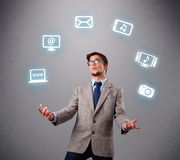 Funny boy juggling with electronic devices icons. Funny boy standing and juggling with electronic devices icons Stock Image