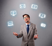 Funny boy juggling with electronic devices icons. Funny boy standing and juggling with electronic devices icons Stock Photo