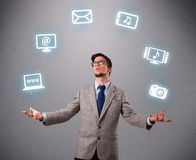 Funny boy juggling with electronic devices icons. Funny boy standing and juggling with electronic devices icons Royalty Free Stock Photo