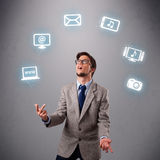 Funny boy juggling with electronic devices icons Royalty Free Stock Photos