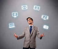 Funny boy juggling with electronic devices icons Stock Photos