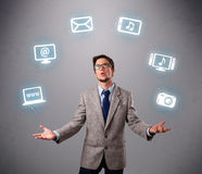 Funny boy juggling with electronic devices icons. Funny boy standing and juggling with electronic devices icons Stock Photography