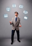 Funny boy juggling with electronic devices icons Royalty Free Stock Photo