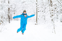 Funny boy jumping in a snowy park Royalty Free Stock Photography