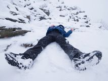 Funny boy laying in snowdrift. Kid play game in fresh snow on stony hill Stock Photo