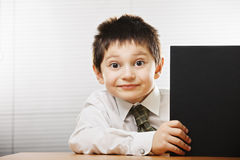 Funny boy looking out of the book. Funny caucasian boy sitting at desk looking out of the big black book Royalty Free Stock Photo