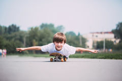 Funny boy lying on a skateboard. Royalty Free Stock Photography
