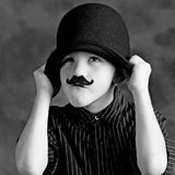 Funny boy with moustache. Black and white portrait of funny boy with moustache pulling bowler hat over ears; studio background Royalty Free Stock Photos