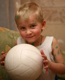 Funny boy with mysterious sight holding white ball Royalty Free Stock Image