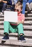 Funny boy playing a laptop in the summer Royalty Free Stock Photos