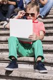 Funny boy playing a laptop in the summer Royalty Free Stock Photo