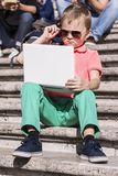 Funny boy playing a laptop in the summer Stock Images