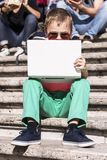 Funny boy playing a laptop in the summer Stock Photos