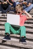 Funny boy playing a laptop in the summer Stock Photo