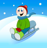 Funny boy rides in a sleigh. Cartoon vector illustration. Stock Photo