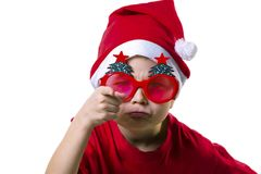 Funny boy Santa Claus in a hat and glasses. With a Christmas tree on a white background Stock Photo