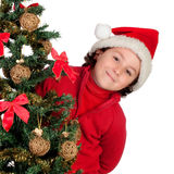 Funny boy with santa hat behind Christmas tree claus. Isolated on white background Royalty Free Stock Photos