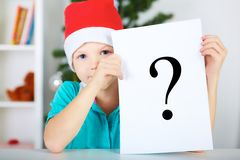 Funny boy in Santa red hat holding a sheet of paper with a question mark sign. Christmas concept Stock Photography