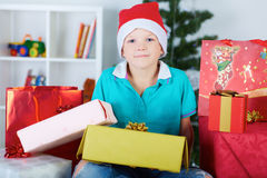 Funny boy in Santa red hat with a lot of gift boxes. Royalty Free Stock Images